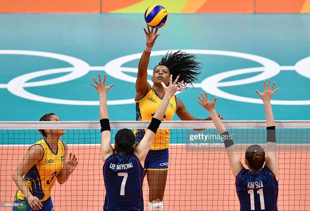 Brazil's Fabiana Claudino (C) spikes the ball during the women's qualifying volleyball match between Brazil and South Korea at the Maracanazinho stadium in Rio de Janeiro on August 12, 2016, during the Rio 2016 Olympic Games. / AFP / PHILIPPE