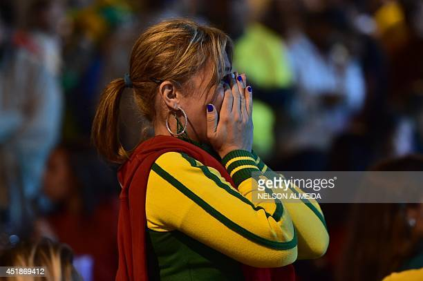 A Brazil's fan reacts during the 2014 FIFA World Cup semifinal match between Brazil and Germany being held at Mineirao Stadium in Belo Horizonte in...