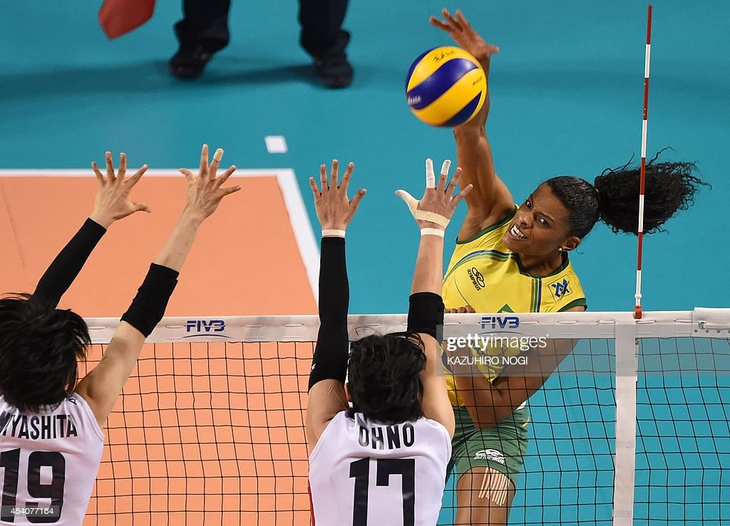 Brazil's Fernanda Rodrigues (R) spikes the ball over Japan's Kana Ono (C) and Haruka Miyashita (L) during their volleyball match at the FIVB Women's World Grand Prix finals in Tokyo on August 24, 2014. Brazil beat Japan 3-0.
