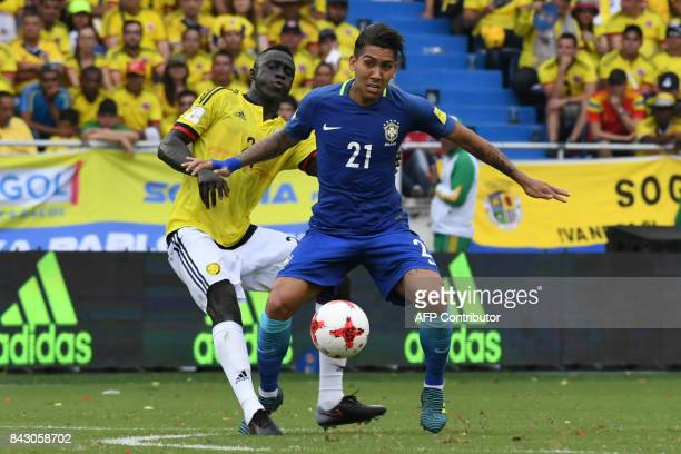 Brazil's Firmino vies for the ball with Colombia's Davinson Sanchez during their 2018 World Cup qualifier football match in Barranquilla Colombia on...