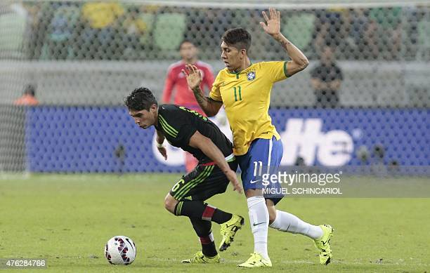 Brazil's Firmino vies for the ball with Mexico's Javier Guemez during a friendly football match in preparation for the Copa America Chile 2015 at...