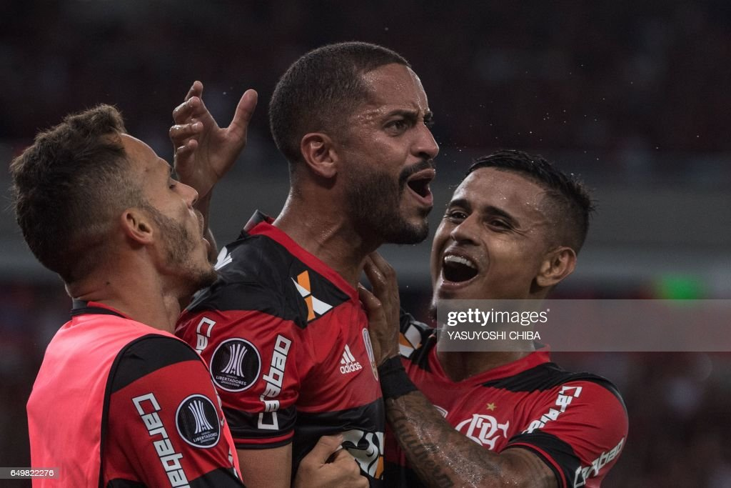 TOPSHOT - Brazil's Flamengo Romulo (C) celebrates with teammate Everton (R) after scoring against Argentina's San Lorenzo during their Libertadores Cup football match at Maracana stadium in Rio de Janeiro, Brazil on March 8, 2017. / AFP PHOTO / Yasuyoshi Chiba