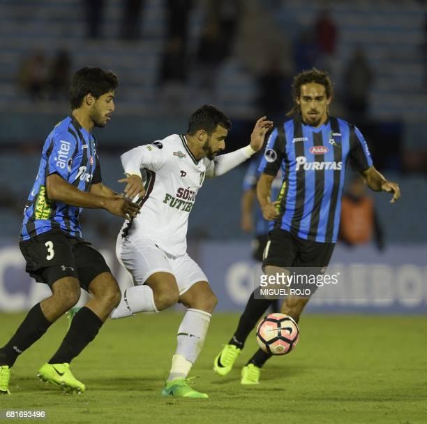 Brazil's Fluminense Henrique Dourado vies for the ball with Uruguay's Liverpool Facundo Mallo and Gustavo Aprile during their Sudamericana Cup...