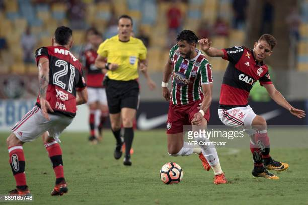 Brazil's Fluminense player Henrique Dourado vies for the ball with Brazil's Flamengo players Para and Gustavo Cuellar during their 2017 Sudamericana...