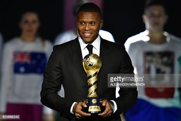 Brazil's football player Julio Baptista arrives on stage with the Confederations Cup trophy prior to the draw for the 2017 FIFA Confederations Cup at...