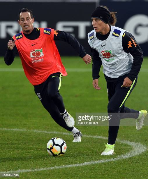 Brazil's football players Rodriguinho Marinho and David Luiz fight for the ball during a training session in Melbourne on June 12 ahead of their...