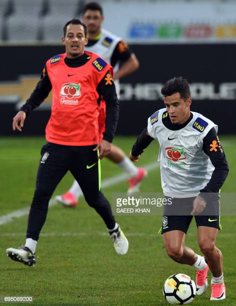 Brazil's football players Rodriguinho Marinho and Philippe Coutinho fight for the ball during a training session in Melbourne on June 12 ahead of...