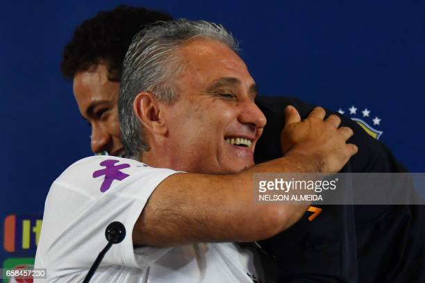 Brazil's footballer Neymar greets team coach Tite during a press conference after a training session on the eve of their 2018 FIFA Russia World Cup...