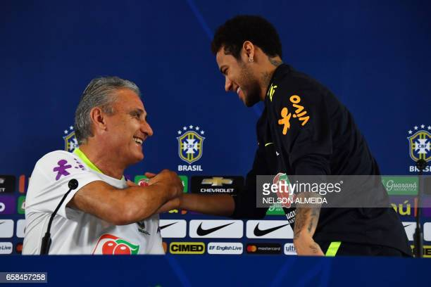 Brazil's footballer Neymar shakes hands with team coach Tite during a press conference after a training session on the eve of their 2018 FIFA Russia...