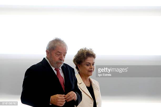 Brazil's former president Luiz Inacio Lula da Silva walks with President Dilma Rousseff as he is sworn in as the new chief of staff in the Planalto...