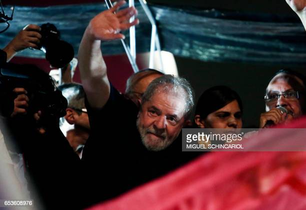 Brazil's former President Luiz Inacio Lula da Silva waves to the crowd as he takes part in a protest during a national strike against the...