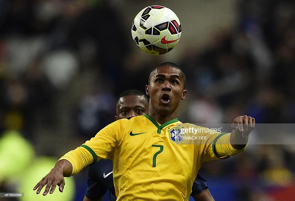Brazil's forward Douglas Costa vies with France's defender Patrice Evra during the friendly football match France vs Brazil on March 26 2015 at the...