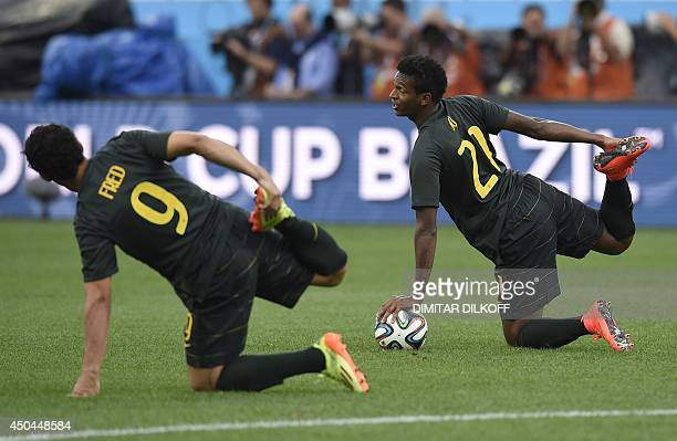 Brazil's forward Fred and Brazil's forward Jo strech during a training session of the Brazilian team at the Corinthians Arena in Sao Paulo on June 11...