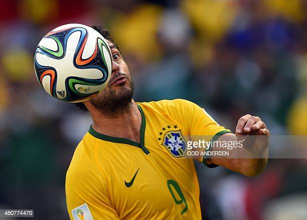 Brazil's forward Fred heads the ball during a Group A football match between Brazil and Mexico in the Castelao Stadium in Fortaleza during the 2014...