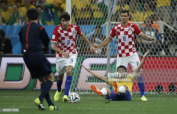 Brazil's forward Fred is fouled by Croatia's defender Dejan Lovren to be awarded a penalty during a Group A football match between Brazil and Croatia...