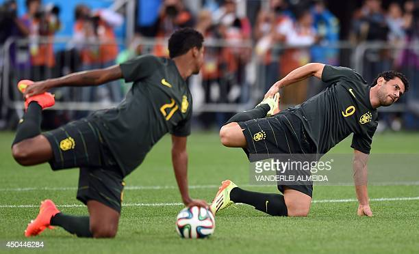 Brazil's forward Jo and Brazil's forward Fred attend a training session of the Brazilian team at the Corinthians Arena in Sao Paulo on June 11 on the...