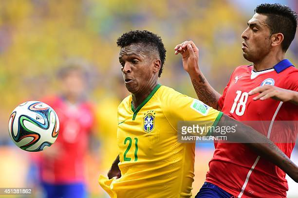 Brazil's forward Jo and Chile's defender Gonzalo Jara vie for the ball during the Round of 16 football match between Brazil and Chile at the Mineirao...