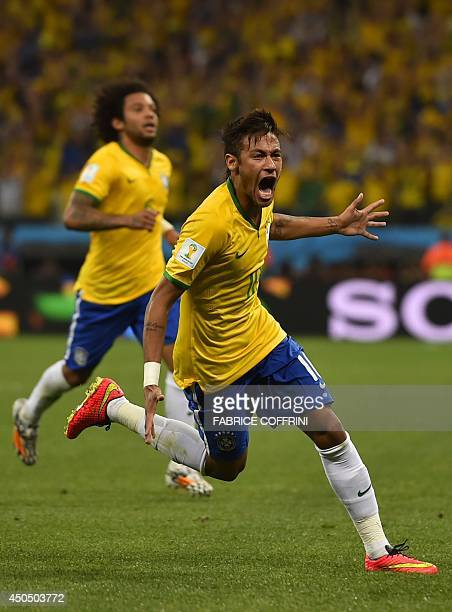 Brazil's forward Neymar celebrates scoring during a Group A football match between Brazil and Croatia at the Corinthians Arena in Sao Paulo during...