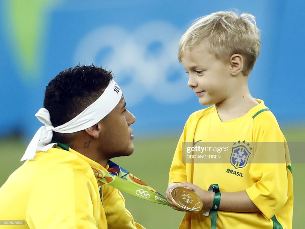 TOPSHOT - Brazil's forward Neymar celebrates with his son after the Rio 2016 Olympic Games men's football gold medal match between Brazil and Germany at the Maracana stadium in Rio de Janeiro on August 20, 2016. / AFP PHOTO / Odd Andersen