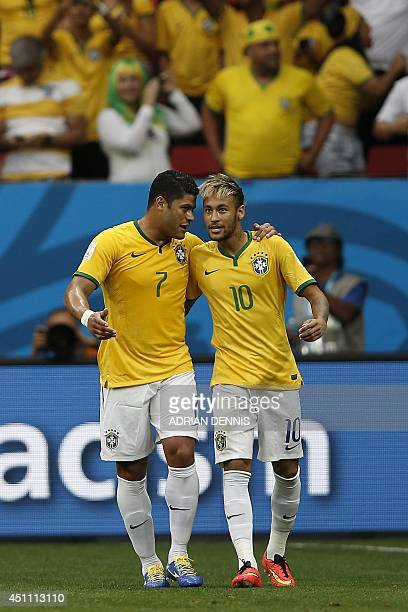 Brazil's forward Neymar celebrates with his temmate Brazil's forward Hulk after scoring a goal during the Group A football match between Cameroon and...