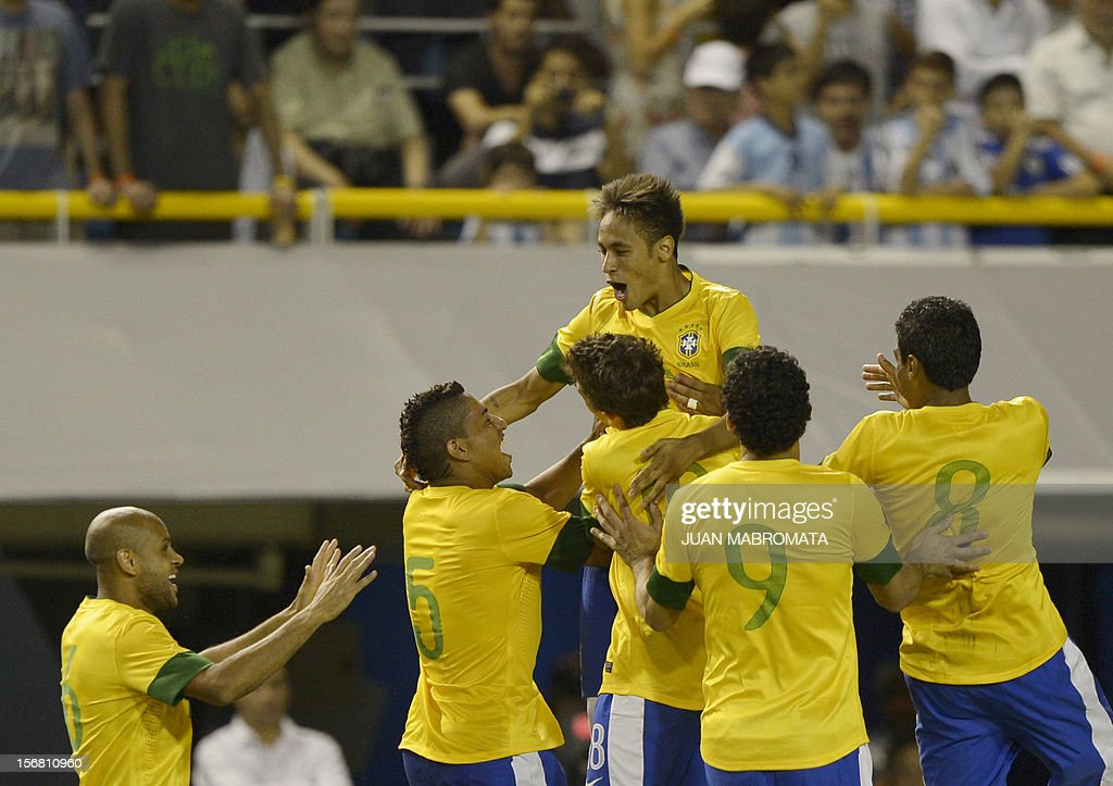 Brazil's forward Neymar (top) celebrates with teammates after scoring the last penalty shoot against Argentina during a friendly football match at Bombonera stadium in Buenos Aires on November 21, 2012. AFP PHOTO / Juan Mabromata