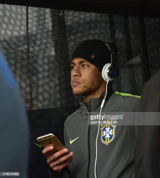 Brazil's forward Neymar checks his mobile phone before the start of the 2015 Copa America football championship match Brazil vs Venezuela at the...