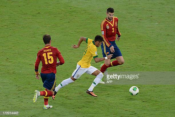 Brazil's forward Neymar drives the ball past Spain's defenders Sergio Ramos and Gerard Pique during their FIFA Confederations Cup Brazil 2013 final...