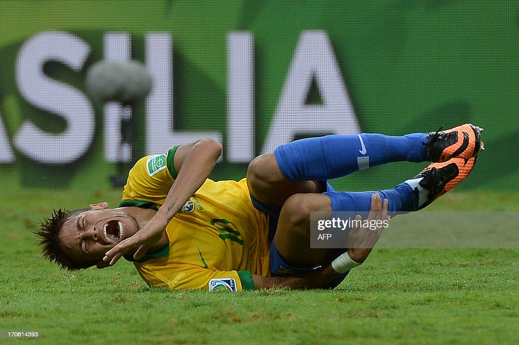 Brazil's forward Neymar gestures on the ground during their FIFA Confederations Cup Brazil 2013 Group A football match against Japan, at the National Stadium in Brasilia on June 15, 2013. AFP PHOTO / YASUYOSHI CHIBA