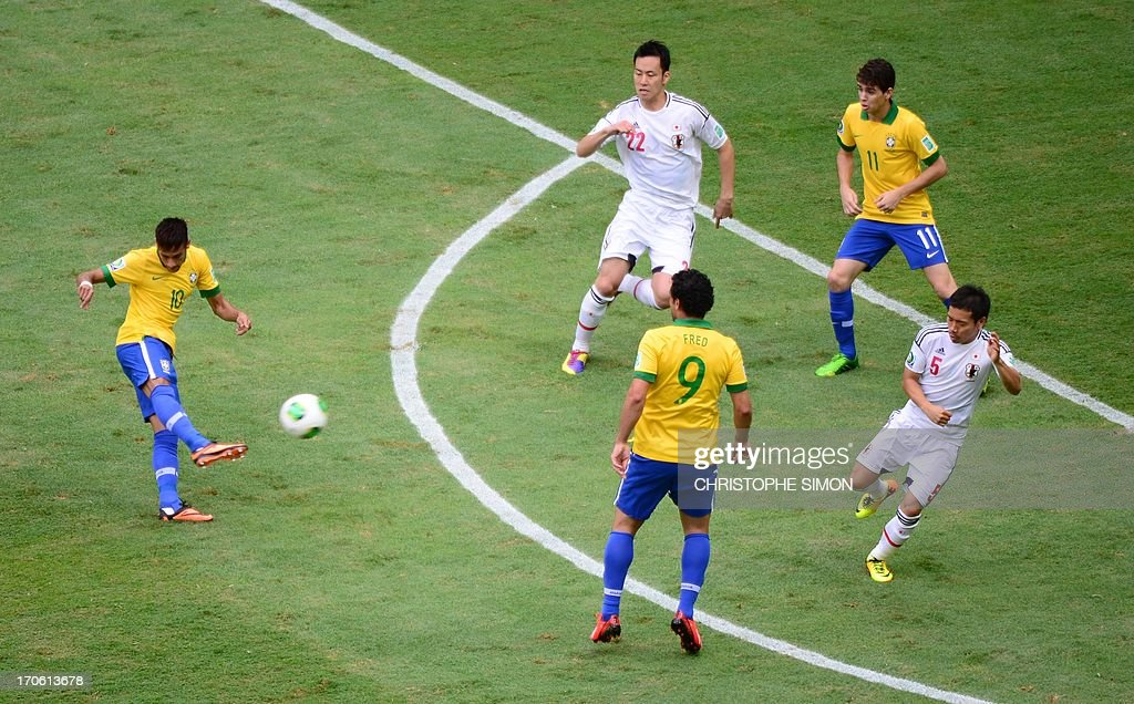 Brazil's forward Neymar (L) kicks the ball to score against Japan during their FIFA Confederations Cup Brazil 2013 Group A football match, at the National Stadium in Brasilia on June 15, 2013.
