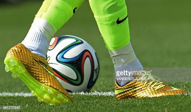 Brazil's forward Neymar participates in a training session wearing a pair of new golden boots adorned with his name and those of his sister and his...