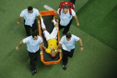 Brazil's forward Neymar reacts in pain as he is carried on a stretcher after being injured during the quarterfinal football match between Brazil and...