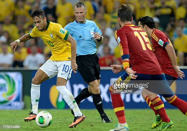 Brazil's forward Neymar takes the ball as Dutch referee Bjorn Kuipers and Spain's defender Sergio Ramos and midfielder Xavi Hernandez look on during...