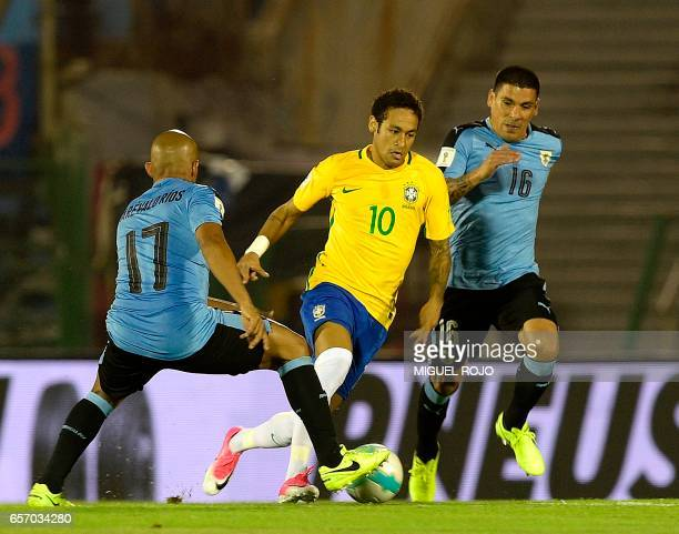 Brazil's forward Neymar vies for the ball with Uruguay's Egidio Arevalo Rios and Maximiliano Pereira during their 2018 FIFA World Cup qualifier...