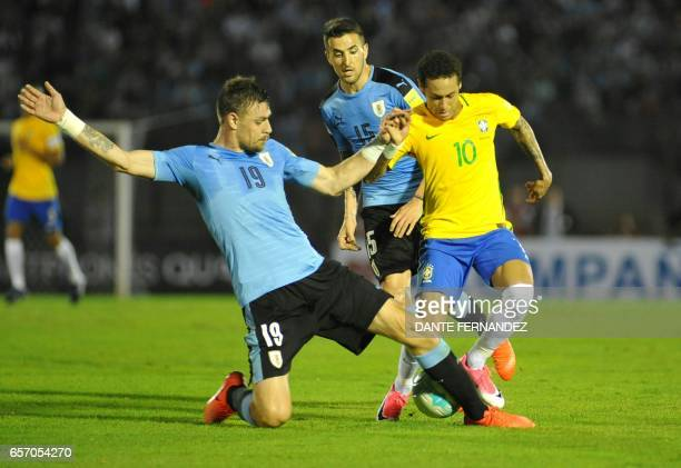 Brazil's forward Neymar vies for the ball with Uruguay's Matias Vecino and Sebastian Coates during their 2018 FIFA World Cup qualifier football match...