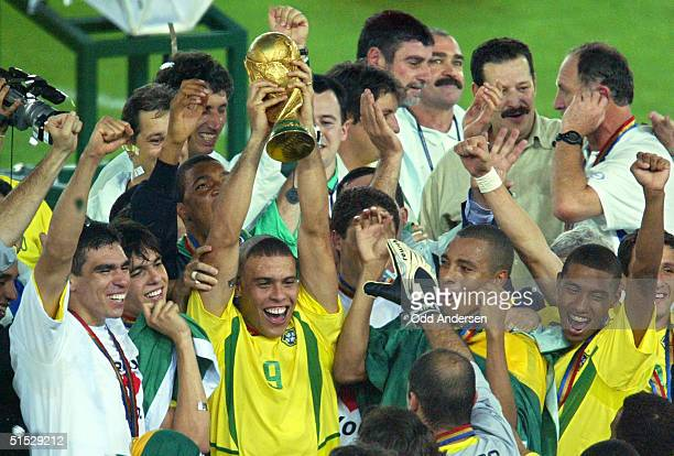 Brazil's forward Ronaldo flanked by teammates hoists the World Cup trophy during the award ceremony at the International Stadium Yokohama Japan 30...