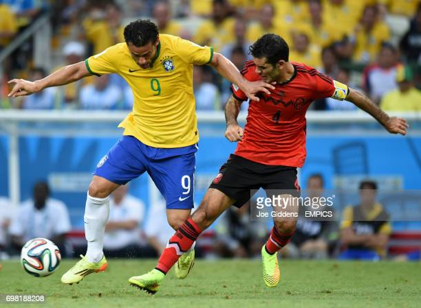 Brazil's Fred battles for the ball with Mexico's Rafael Marquez
