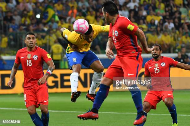 Brazil's Gabriel Jesus heads the ball as Chile's Gonzalo Jara Gary Medel and Jean Beausejour look on during their 2018 World Cup football qualifier...