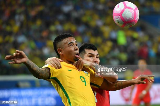 Brazil's Gabriel Jesus is grabbed by Chile's Gary Medel during their 2018 World Cup football qualifier match in Sao Paulo Brazil on October 10 2017 /...