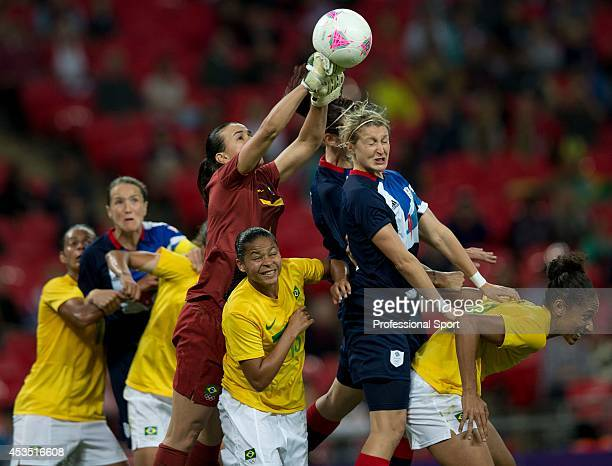 Brazil's goalkeeper Andreia punches the ball away under pressure from Great Britain's Ellen White during the London 2012 Olympic women's preliminary...