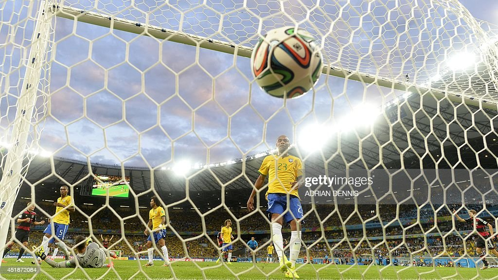 Brazil's goalkeeper Julio Cesar (L bottom) concedes a goal during the semi-final football match between Brazil and Germany at The Mineirao Stadium in Belo Horizonte during the 2014 FIFA World Cup on July 8, 2014. Germany won 7-1.