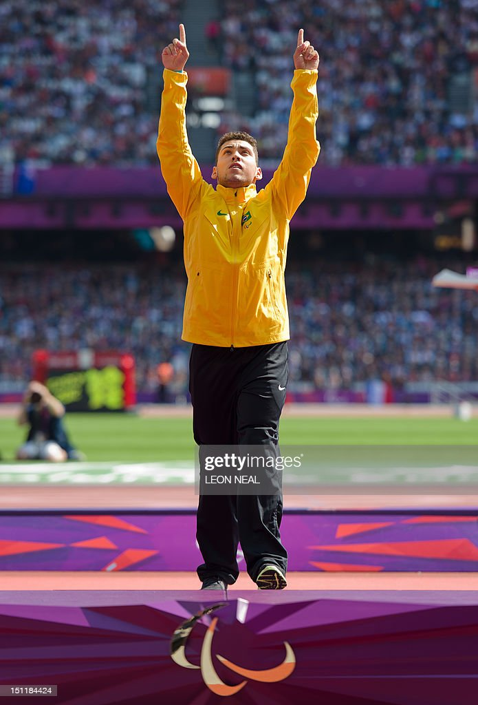 Brazil's gold medallist Alan Oliveira steps onto the podium during the medal ceremony of the men's 200m T44 athletics event at the London 2012 Paralympic Games at the Olympic Stadium in east London on September 3, 2012. South Africa's Oscar Pistorius apologised on September 3 for the timing of his outburst after losing his T44 200m title, but insisted there was an issue with large prosthetics lengthening an amputee's stride. Pistorius, the star of the London 2012 Paralympics, was sensationally beaten into the silver medal position by Brazil's Alan Oliveira on September 2, in a result that stunned the Olympic Stadium. The 25-year-old then hit out at the International Paralympic Committee (IPC), claiming it was not a fair race and he was at a disadvantage caused by artificial leg length, as the regulations allowed athletes to make themselves 'unbelievably high'. AFP PHOTO / LEON NEAL