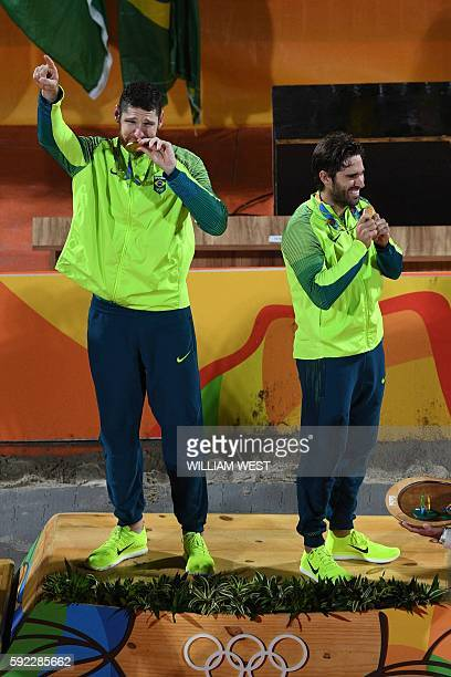 Brazil's gold medallists Alison Cerutti and Bruno Oscar Schmidt celebrate on the podium at the end of the men's beach volleyball event at the Beach...