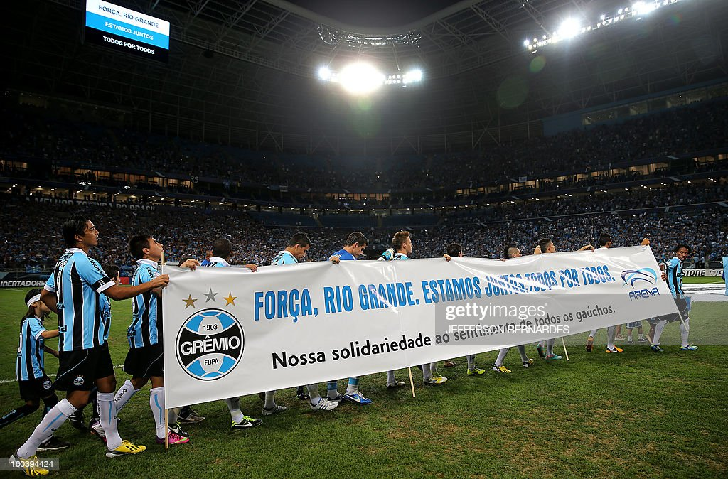 Brazil's Gremio football team enters the field carrying a banner in homage to the victims of a fire in Santa Maria, before the start of their Copa Libertadores match at the Arena do Gremio stadium in Porto Alegre, Brazil, on January 30, 2013. AFP PHOTO / Jefferson BERNARDES