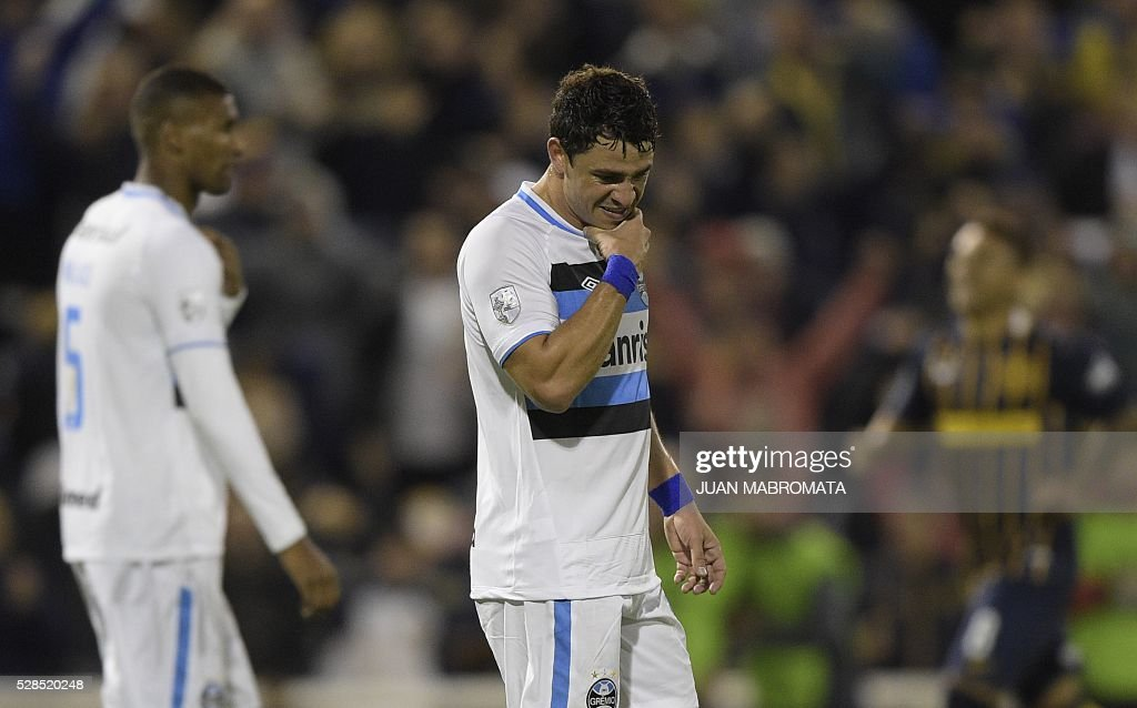 Brazil's Gremio midfielder Giuliano (R) and defender Fred (L) react after Argentina's Rosario defender Alejandro Donatti scored during their Copa Libertadores 2016 round before the quarterfinals second leg football match at the 'Gigante de Arroyito' stadium in Rosario, Santa Fe, Argentina, on May 5, 2016. / AFP / JUAN