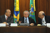 Brazil's interim President Michel Temer gestures between Chief of Staff Eliseu Padilha and Economy Minister Henrique Meirelles during the first...