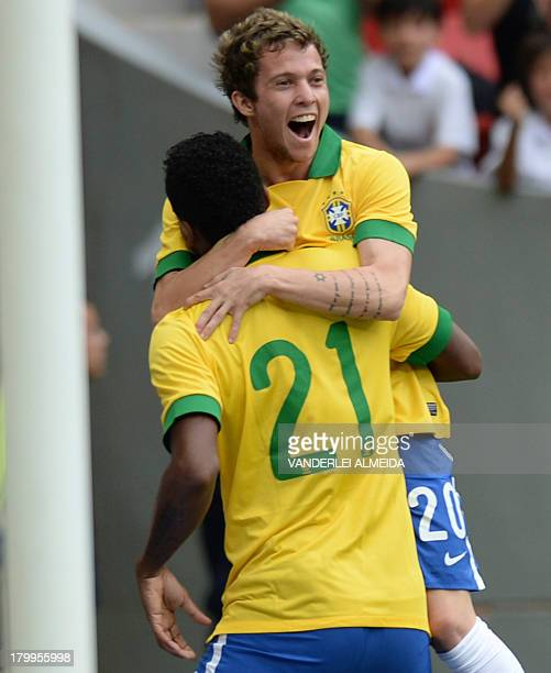 Brazil's Jo celebrates with teammate Bernard after scoring against Australia during their friendly football match at the Mane Garrincha National...