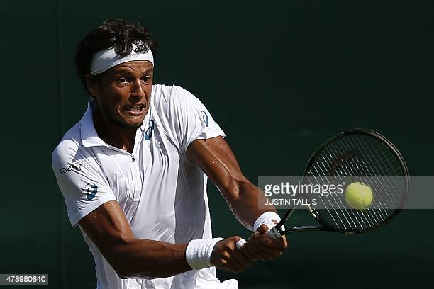Brazil's Joao Souza returns against Colombia's Santiago Giraldo during their men's singles first round match on day one of the 2015 Wimbledon...
