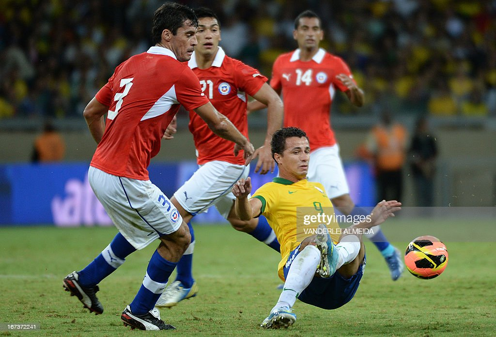 Brazil's Leandro Damiao (R) vies for the ball with Marcos Gonzalez (L) of Chile, during their friendly football match at the Mineirao stadium, in Belo Horizonte, Minas Gerais, Brazil, on April 24, 2013. AFP PHOTO / VANDERLEI ALMEIDA