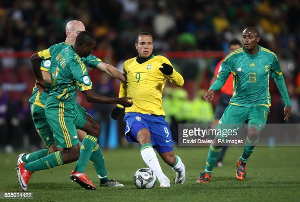 Brazil's Luis Fabiano holds of challenges from South Africa's Matthew Booth Aaron Mokoena and Kagisho Evidence Dikgacoi