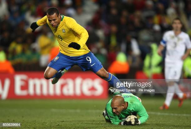 Brazil's Luis Fabiano jumps over USA's goalkeeper Tim Howard after he saves his shot on goal